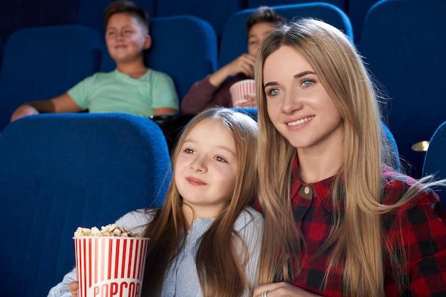 Mooie moeder en dochter kijken naar film in de bioscoop.
