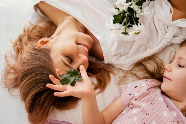 Mooie moeder en dochter met boeket van delicate lentebloemen