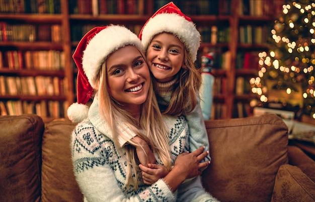 Mooie moeder en dochter, met kerstmutsen op, kerstboomverlichting. portret vakantie.