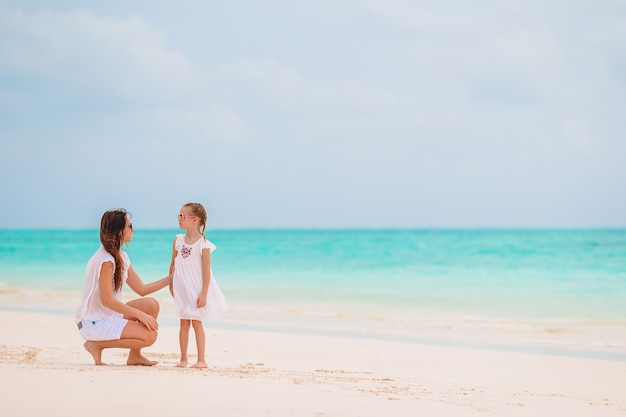 Mooie moeder en dochter op caribisch strand genieten van zomervakantie.