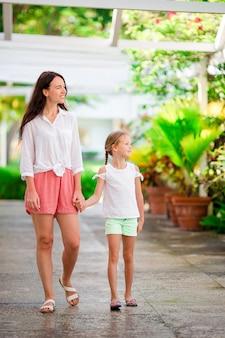 Mooie moeder en dochter op caribisch strand genieten van zomervakantie