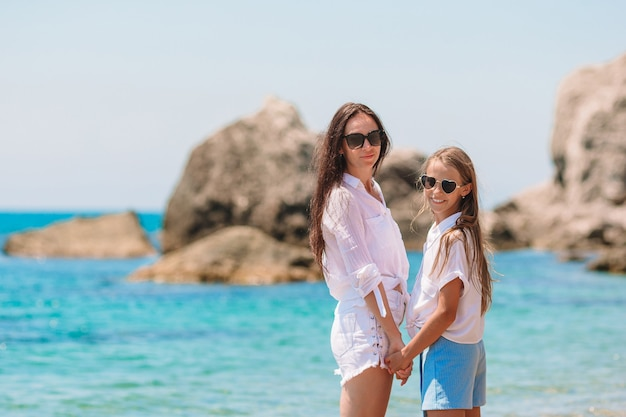 Mooie moeder en dochter op het strand die van de zomervakantie genieten.