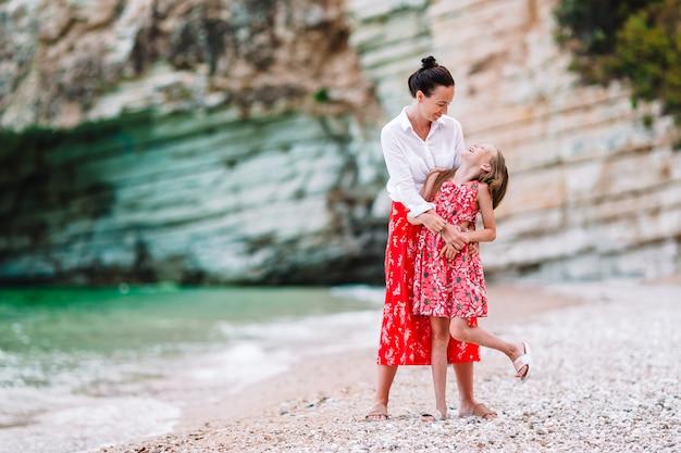 Mooie moeder en dochter op het strand genieten van zomervakantie.