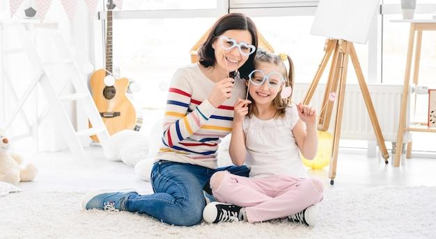 Mooie moeder en dochter spelen met stoklippen en glazen