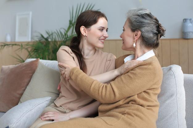 Mooie moeder en dochter. vrolijke jonge vrouw omhelst haar moeder van middelbare leeftijd in de woonkamer. familie portret.