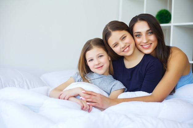 Mooie moeder en dochters knuffelen, kijken en glimlachen terwijl ze thuis op bed zitten