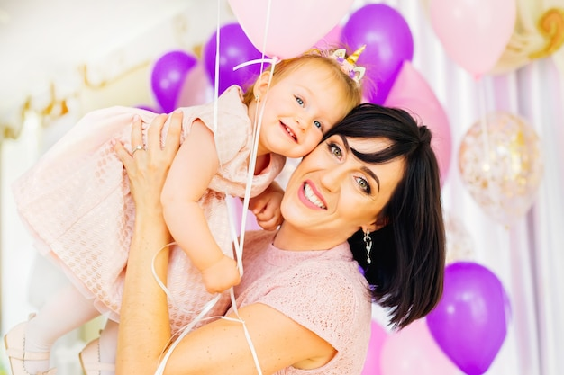 Mooie moeder en dochtertje bij de viering van de verjaardag van een kind in een restaurant dat is versierd met verschillende decoraties