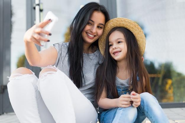 Mooie moeder en dochtertje maken selfie foto door smartphone