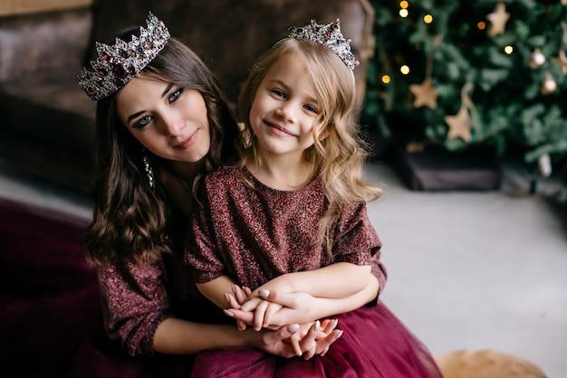 Mooie moeder en haar dochter in de afbeelding van de koningin en de prinses in de marsala-kleurige jurk