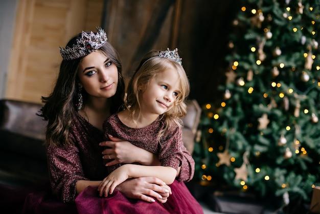 Mooie moeder en haar dochter naar het beeld van de koningin en de prinses in de marsala-kleurige jurk met een lange trein op het hok
