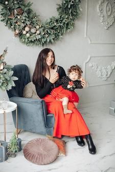 Mooie moeder en haar schattige dochtertje zitten in een fauteuil onder de kerstkrans