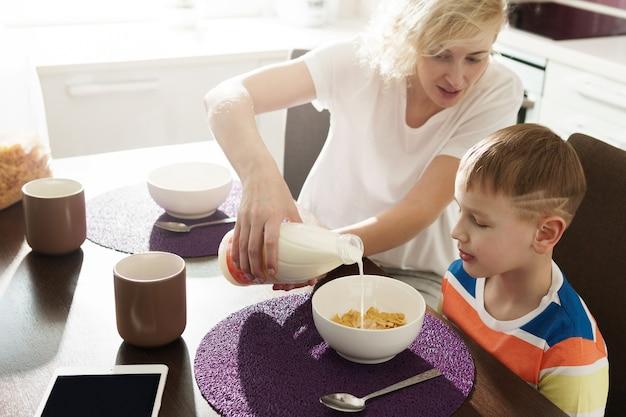 Mooie moeder en haar schattige zoon die gezonde cornflakes eten als ontbijt