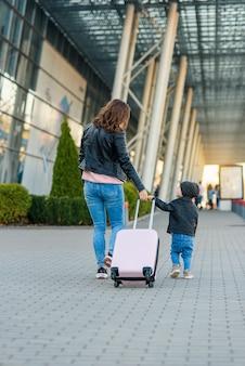 Mooie moeder en haar stijlvolle schattige dochter lopen samen en trekken een roze koffer naar het vliegveld.