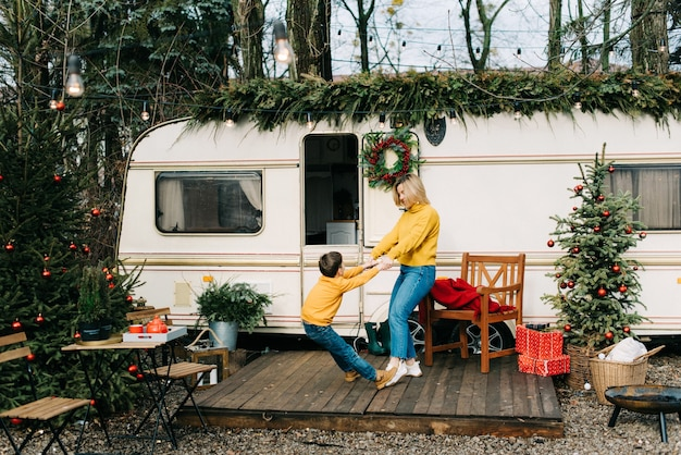 Mooie moeder en kindjongen met rode kopjes drinken cacao of thee in aanhangwagen