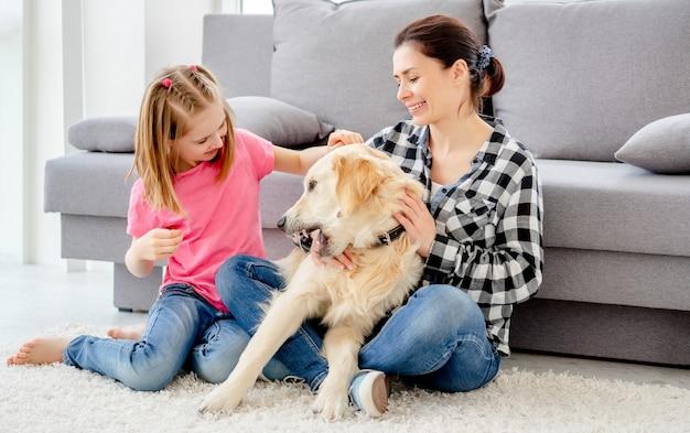 Mooie moeder en schattige dochter spelen met schattige hond thuis