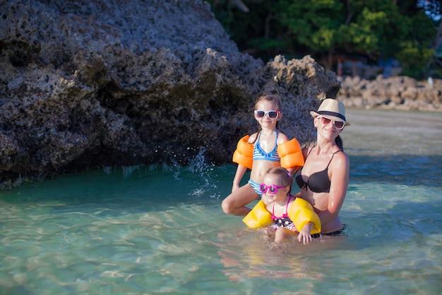 Mooie moeder en twee haar kinderen op exotisch strand op zonnige dag