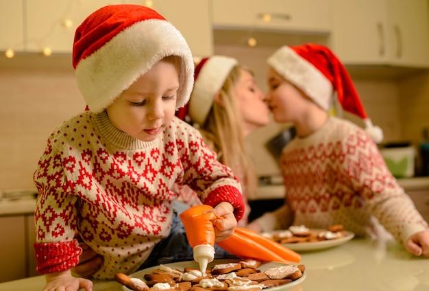 Mooie moeder en zoontjes versieren zelfgemaakte gebakken peperkoek kerstkoekjes, hagelslag toevoegen, genieten van proces aan tafel in de keuken.