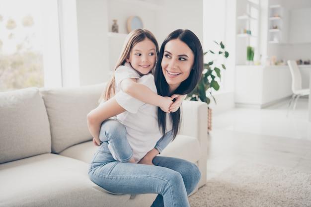 Mooie moeder houdt haar schattige kleine meisje kind spel meeliften in de kamer
