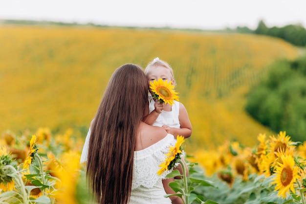 Mooie moeder knuffelen met de dochter op het gebied van zonnebloemen. vrouw met lang haar en babymeisje plezier buitenshuis. familie concept. zomervakantie
