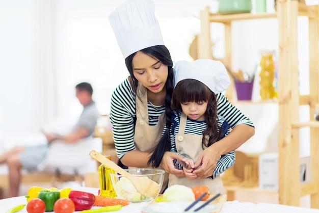 Mooie moeder leert haar dochter schoffel om ontbijt in de keuken te bereiden