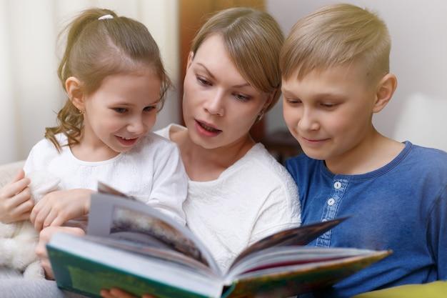 Mooie moeder leest een boek voor haar jonge kinderen. zus en broer luisteren naar een verhaal. gelukkig liefdevolle familie.