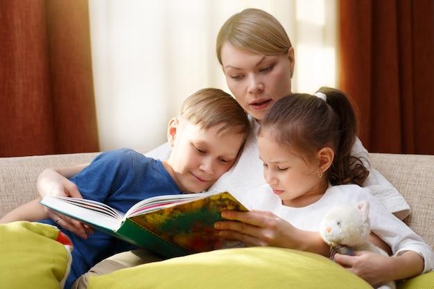 Mooie moeder leest een boek voor haar jonge kinderen