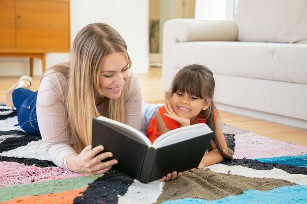 Mooie moeder liggend op tapijt met dochter en leesboek aan haar.