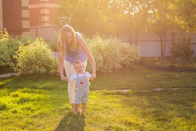Mooie moeder loopt met haar zoontje van de babyjongen met eerste stappen