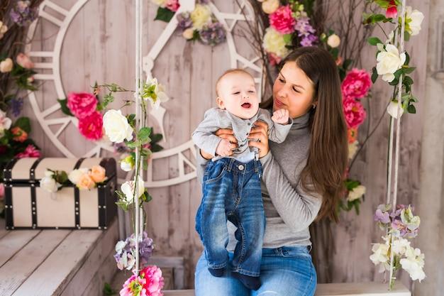 Mooie moeder met babyjongen, moeder draagt schattig kind schattige kleine zoon, gelukkige familiefoto, moeder en kind binnen, geluksconcept