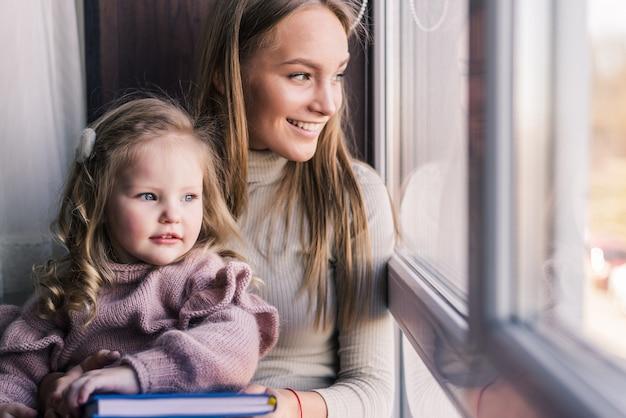 Mooie moeder met dochter. familiezitting in de ruimte dichtbij venster die buiten eruit zien