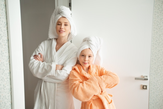 Mooie moeder met dochter in badjassen binnenshuis