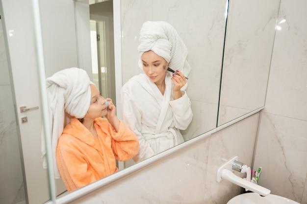 Mooie moeder met dochter in badjassen in de badkamer bij de spiegel
