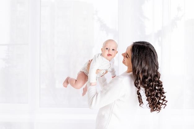 Mooie moeder met een baby in haar armen bij het raam van het huis, het concept van een liefdevolle en gelukkige familie, levensstijl