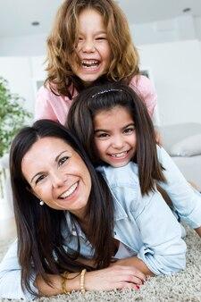 Mooie moeder met haar dochters thuis kijken naar de camera.