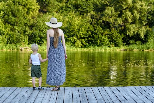Mooie moeder met haar zoontje staan op de pier bij de rivier. achteraanzicht