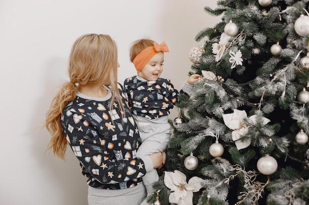 Mooie moeder met kind. familie in kerstsfeer. mensen die kerstboom dragen.