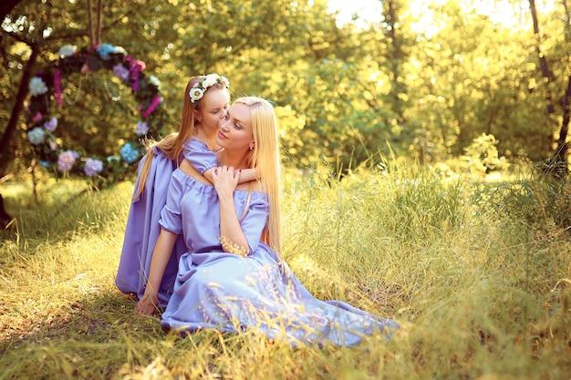 Mooie moeder met lang blond haar poseren en spelen met haar dochter in soortgelijke lavendel jurken in het park buiten