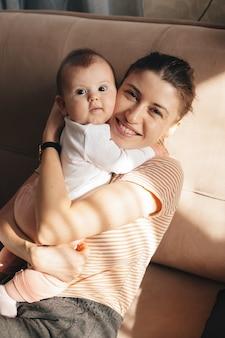 Mooie moeder met sproeten omhelst haar dochter glimlachend in de camera
