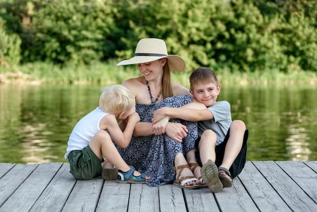 Mooie moeder met twee jonge zonen omarmen op de pier op de oever van de rivier