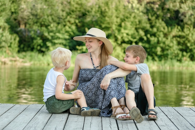 Mooie moeder met twee jonge zonen zit op de pier aan de rivieroever.