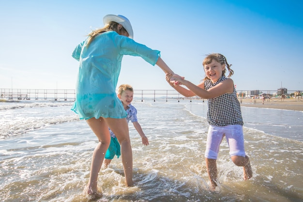 Mooie moeder speelt met haar kinderen in de zee