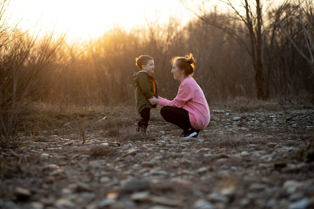 Mooie moeder speelt met haar zoon in de natuur tegen zonsondergang. moederdag concept.