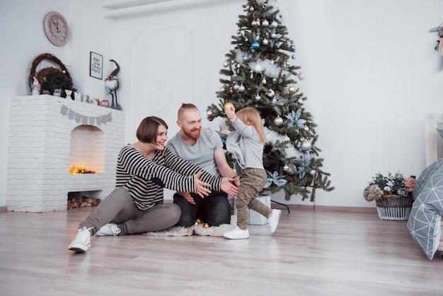 Mooie moeder, vader en dochter gebruiken een laptop en glimlachen terwijl ze in de buurt van kerstcadeautjes zitten