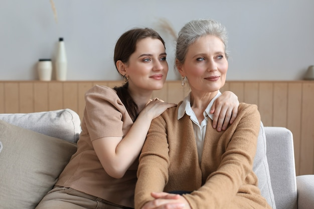 Mooie moeder van middelbare leeftijd en haar volwassen dochter knuffelen, kijken weg en glimlachen.