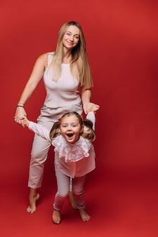 Mooie moeder veel plezier met haar mooie dochter en glimlach, foto geïsoleerd op rode achtergrond