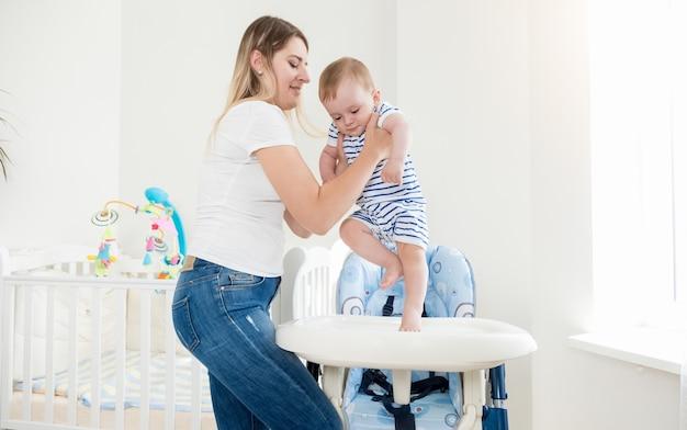 Mooie moeder zet haar zoontje in de kinderstoel