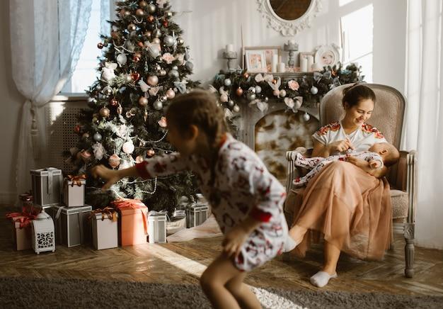 Mooie moeder zit in de fauteuil met haar kleine baby naast de open haard en de nieuwjaarsboom met geschenken in de lichte, gezellige kamer en haar dochtertje rent rond. .