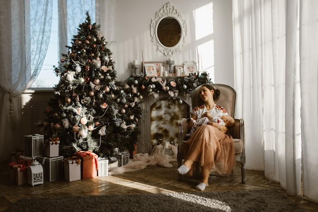 Mooie moeder zit in de fauteuil met haar kleine baby naast de open haard en de nieuwjaarsboom met geschenken in de lichte, gezellige kamer.