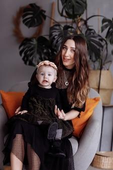 Mooie moeder zit op een stoel en houdt haar dochter op schoot thuis. familie look concept. moederdag, baby's dag.