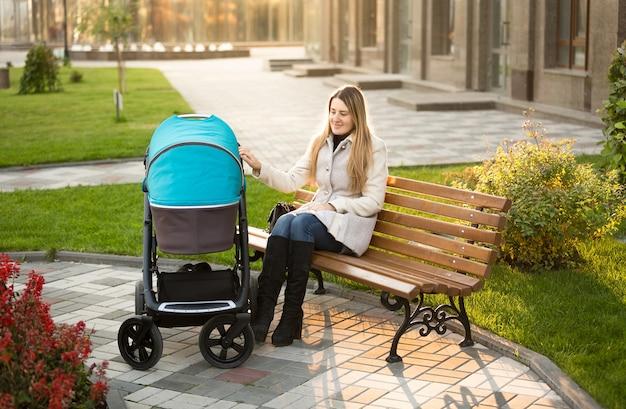 Mooie moeder zittend op een bankje in het park en wuivende kinderwagen